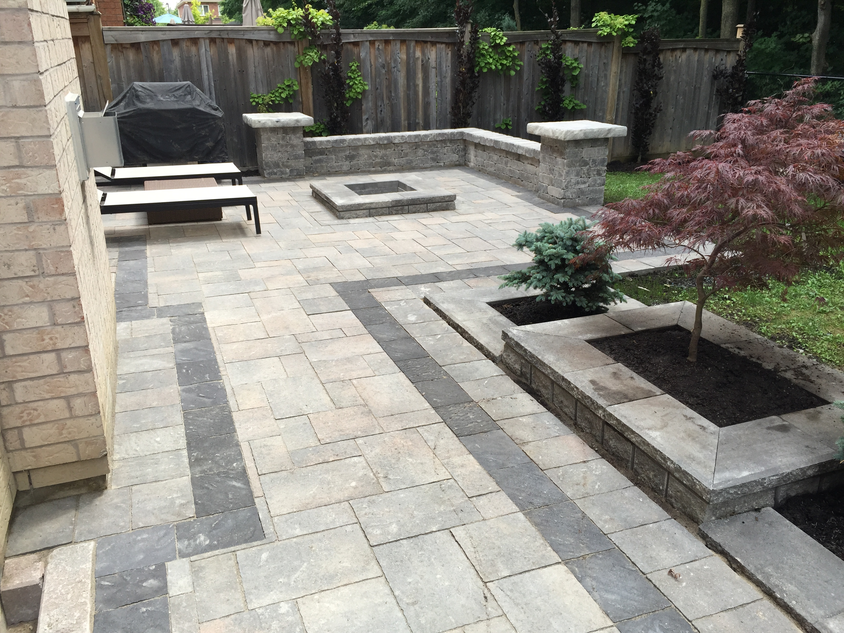 Beautiful Stone Back Patio and Entertainment Area with Interlocking Stone Pattern