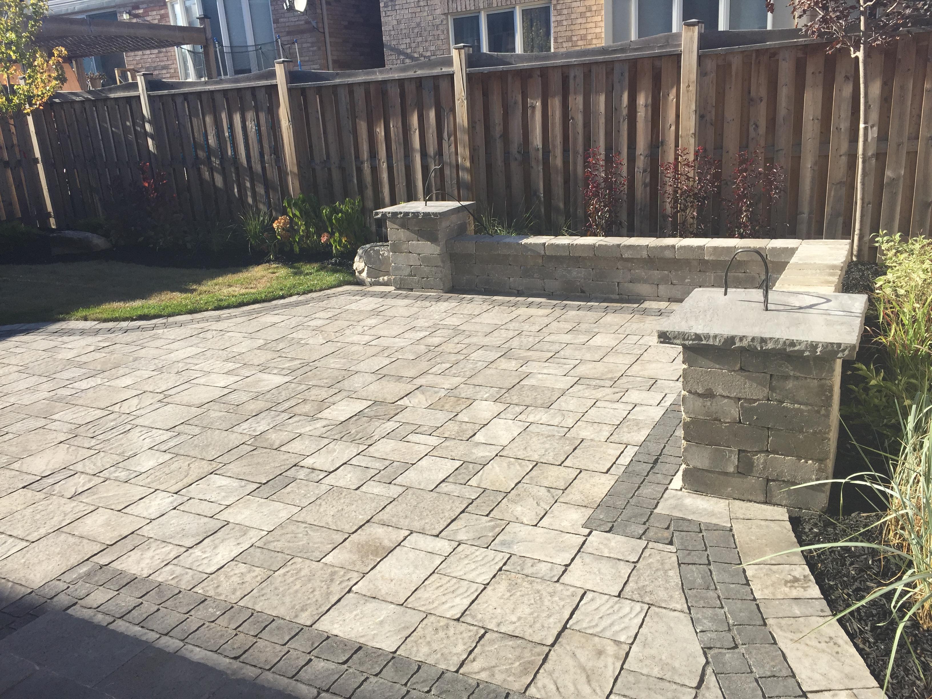 Backyard Interlocking Stone Patio With Corner Wall